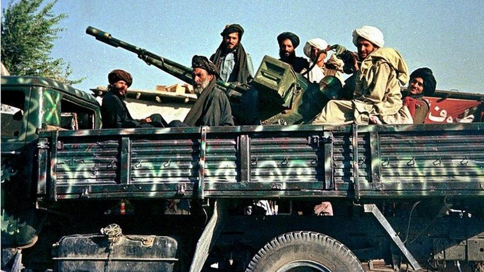 Afghan Taliban soldiers 28 July 2000 pose in Kabul on their newly-painted military truck with their anti-aircraft gun on the way to the frontlines north of the capital.