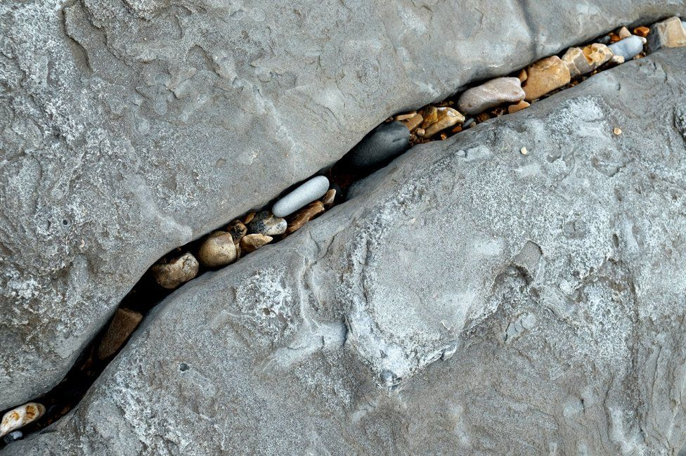 Smaller pebbles and stones sit in between the cracks of larger rocks