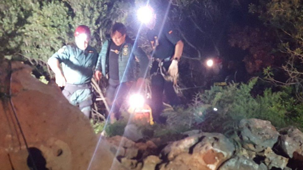 Xisco Gràcia being helped from the cave by two rescuers