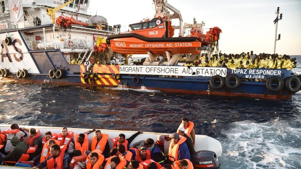 Members of Maltese NGO MOAS help people to board a small rescue boat during a rescue operation of migrants and refugees by the Topaz Responder ship run by Maltese NGO Moas and the Italian Red Cross, on November 5, 2016
