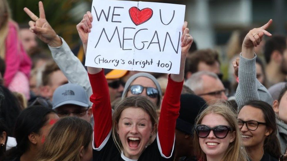 """A fan with a """"we love you Meghan"""" sign"""