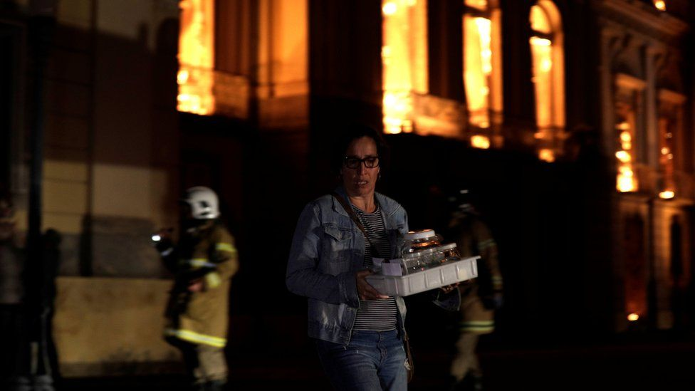A worker rescues items during a fire at the National Museum of Brazil in Rio de Janeiro, Brazil on 2 September 2018