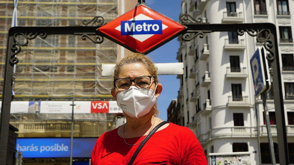 A woman wearing a mask outside a metro station in Madrid