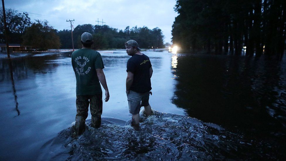 Two men stand in knee deep waters on a highway in Kinson, North Carolina