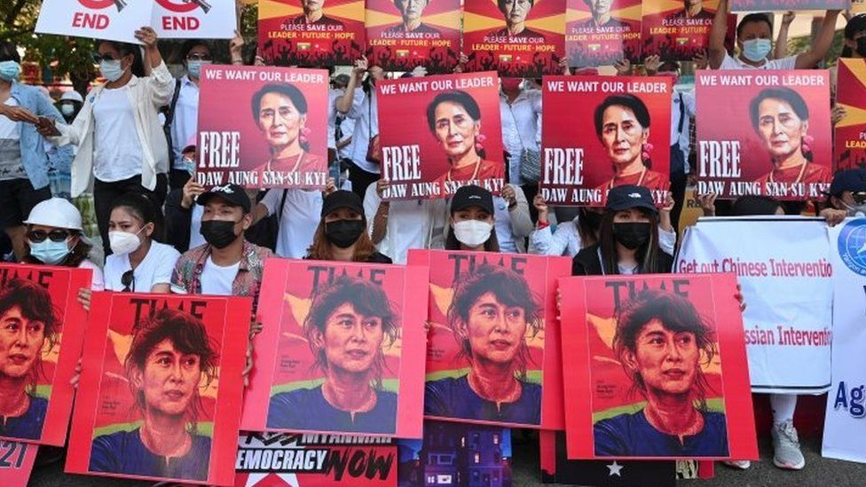 Protesters in Myanmar hold up signs showing jailed leader Aung San Suu Kyi