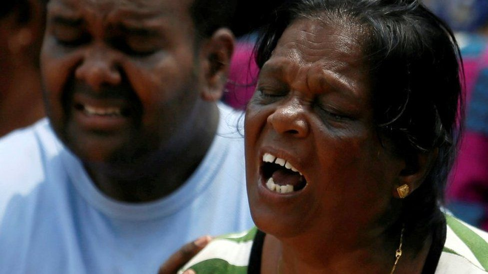Family members of victims react during a rescue mission after a garbage dump collapsed and buried dozens of houses in Colombo