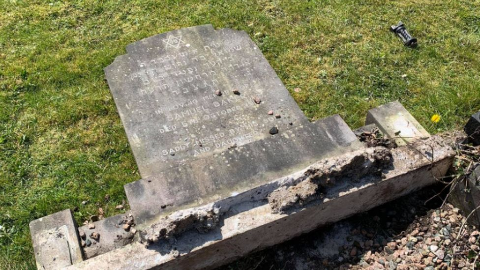 An image showing one of the gravestones laid down flat, with a star of David visible above Hebrew lettering