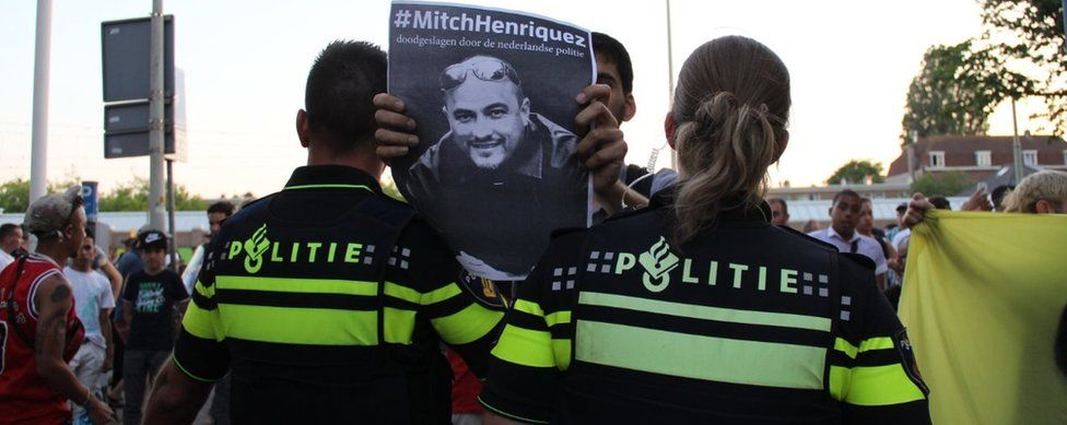 Protester holds up placard of Aruba-born Mitch Henriquez who died in June 2015