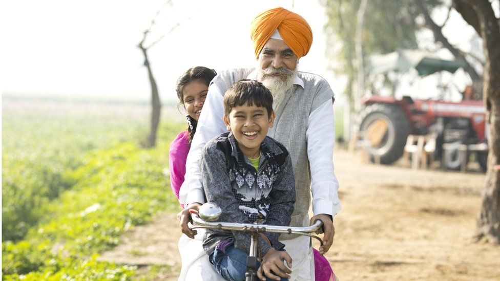 A man with a grey beard and a turban on a bike with two young children