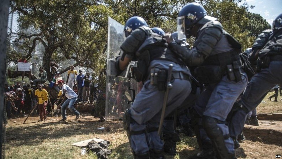police hide behind shields as student protesters throw missiles