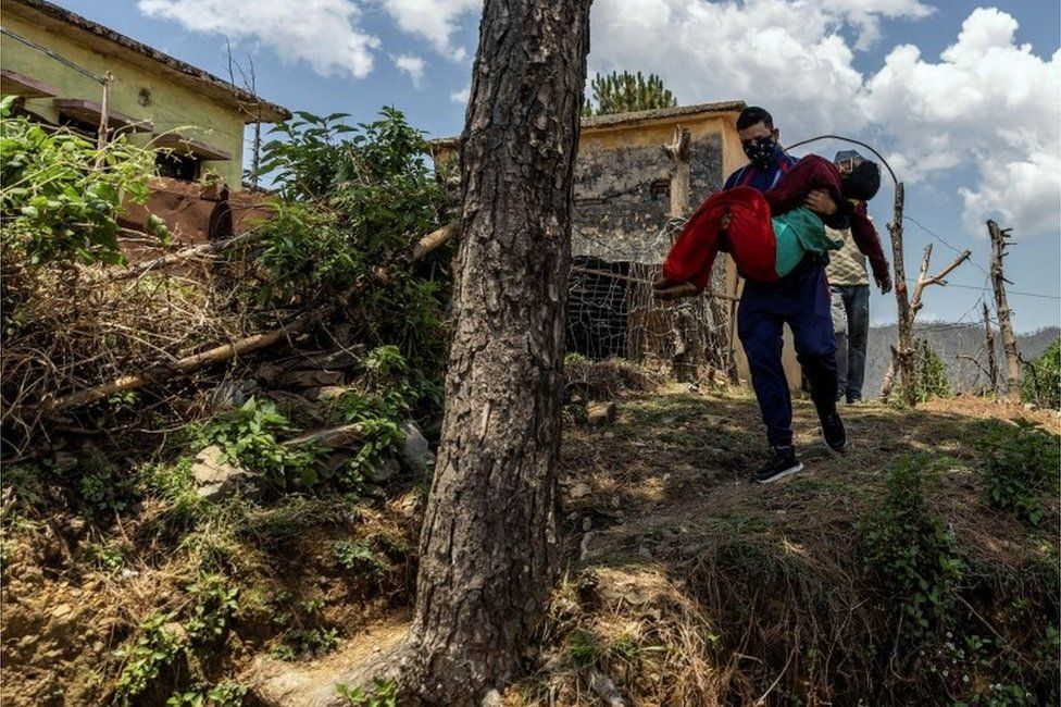 Pramila Devi, 36, who is suffering from the coronavirus disease (COVID-19), is carried by her nephew Rajesh Kumar, as he takes her to a local government dispensary, in Kaljikhal, in the northern state of Uttarakhand, India, May 23, 2021