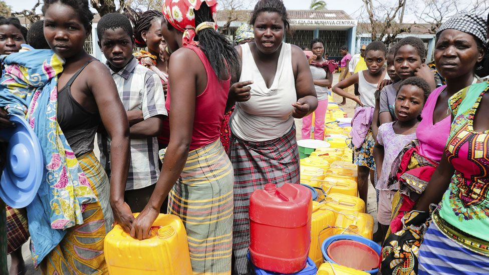 People wait to collect drinkable water delivered by local authorities after the cut on public supply of water that followed the passage of the cyclone Idai in Beira City, central Mozambique, 21 March 2019.