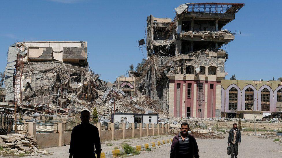 People walk past destroyed University of Mosul buildings (11 July 2017)