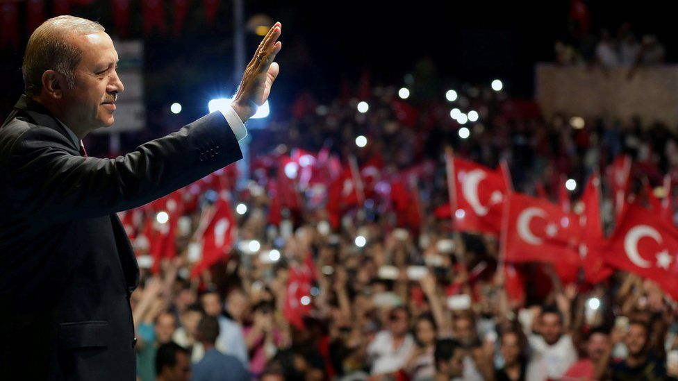 Turkish President Tayyip Erdogan greets his supporters outside of his residence in Istanbul, Turkey, early July 19, 2016, in this handout photo provided by the Presidential Palace
