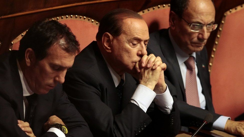 Mr Berlusconi sat with his hands crossed, flanked by two men