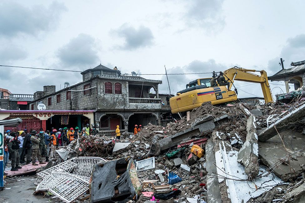 A bulldozer clears the rubble of a building that collapsed in the earthquake in Brefet, a neighborhood of Les Cayes, Haiti, on 17 August 2021