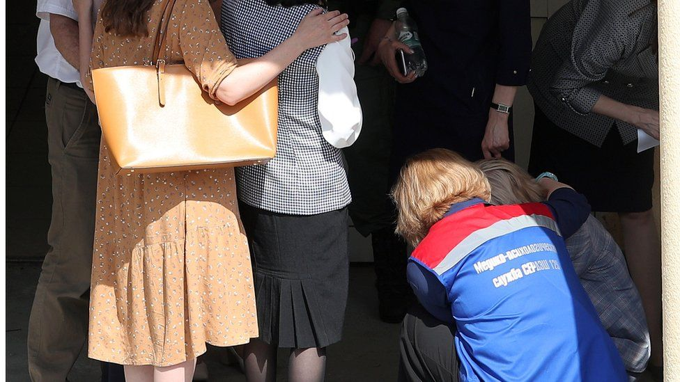 A medical worker comforts relatives of students of School No 175 in Kazan, 11 May