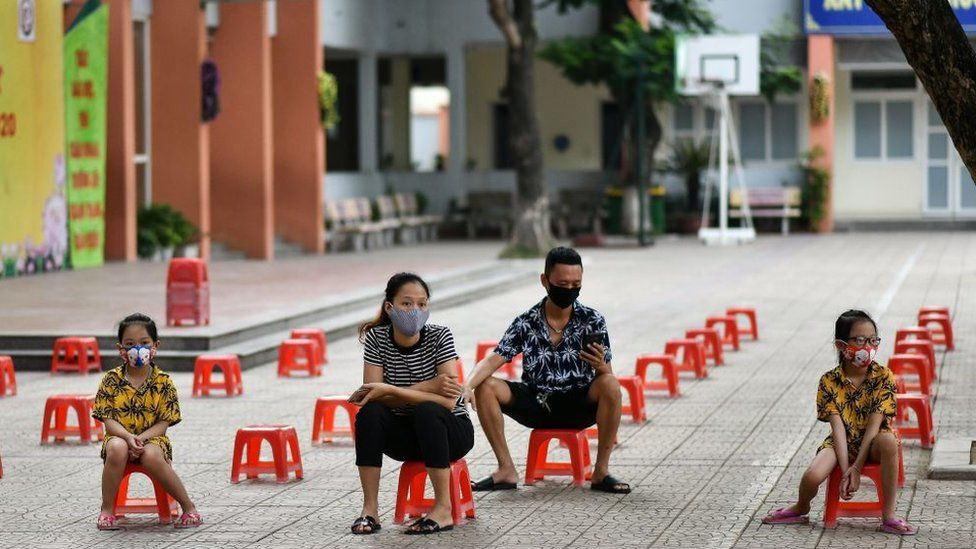 A family sit on plastic stools as they wait to be tested at a makeshift rapid testing centre as Vietnam records a rise in cases of the COVID-19 coronavirus in Hanoi on July 31, 2020.