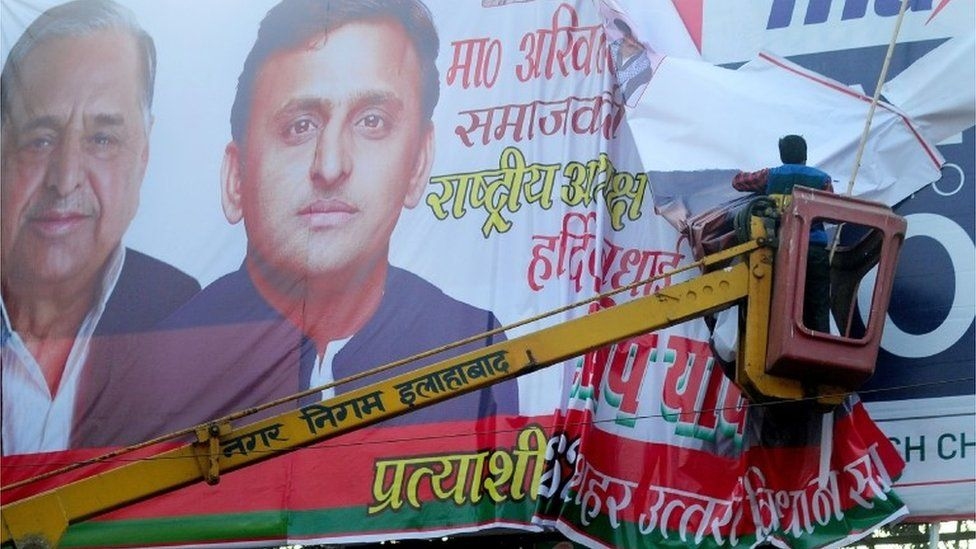 An Indian worker from the municipal corporation and Allahabad administration removes a banner poster of Uttar Pradesh chief minister, Akhilesh Yadav and his father Mulayam Singh Yadav at the roadside in Allahabad on January 4, 2016.