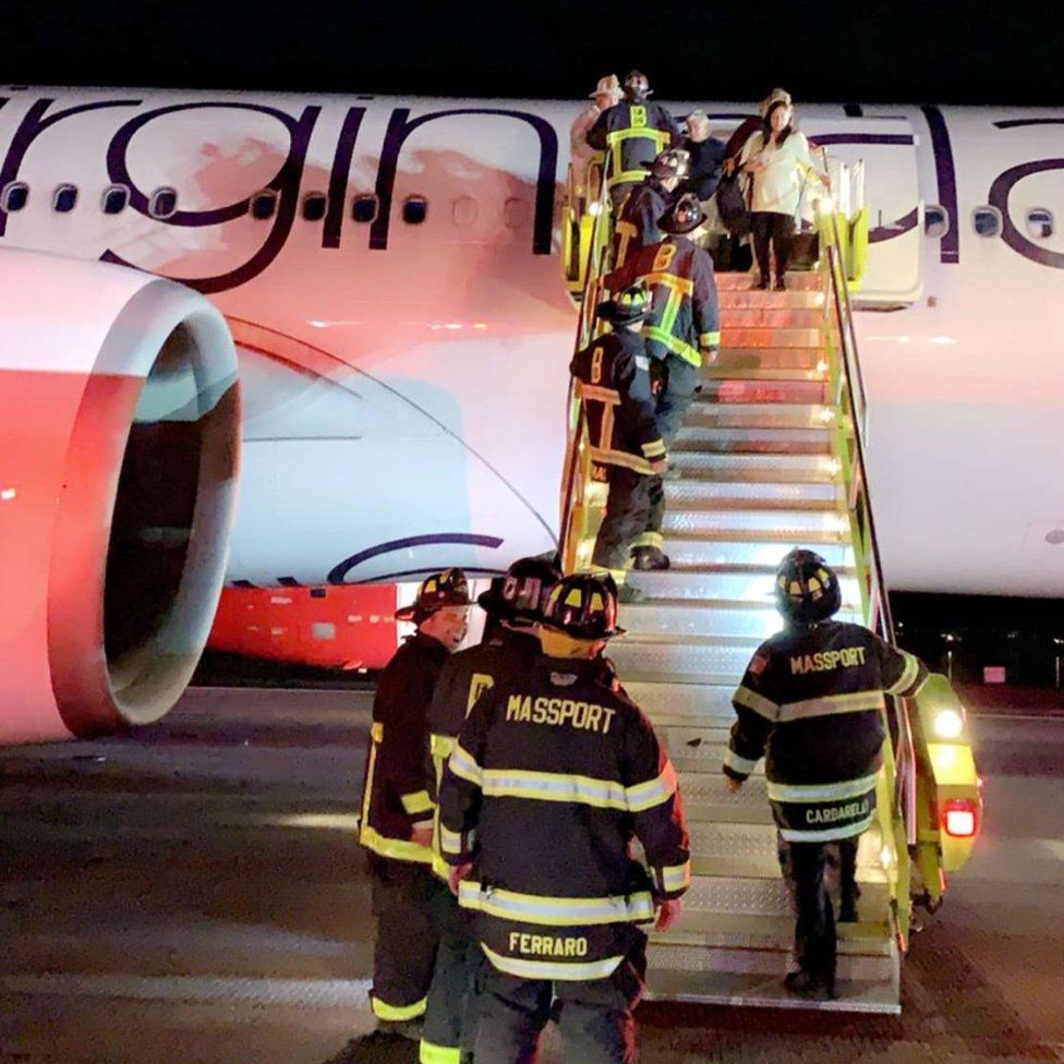 Firefighters board a Virgin Atlantic plane on the runway