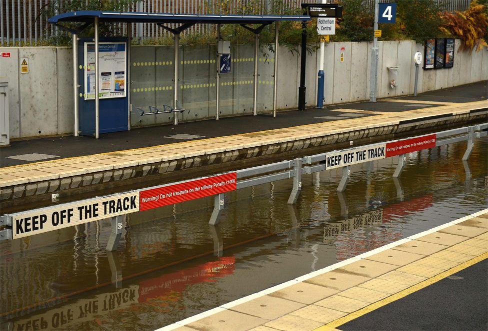 Uji i përmbytjes që mbulon shinat hekurudhore në stacionin e trenit Qendror Rotherham