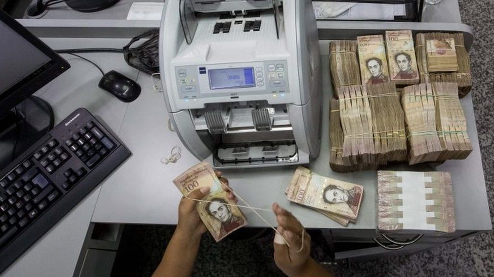 A bank worker counts 100 Bolivar bills in Caracas, Venezuela, 15 December 2016.