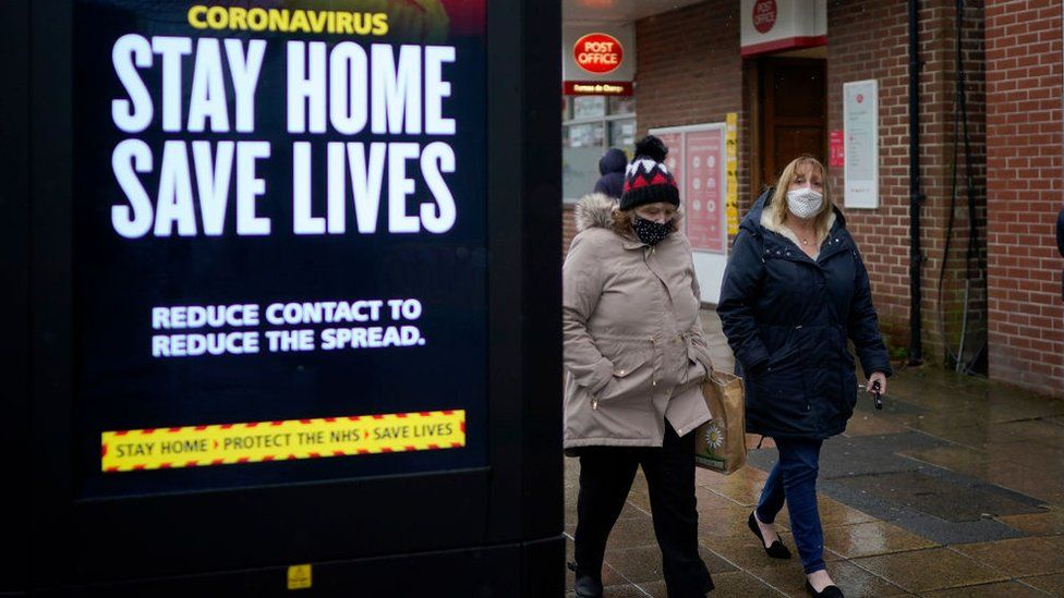 Two women walk past a stay home sign in Hyde, Greater Manchester