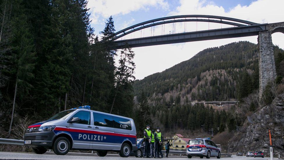 A police officer with protective gear at a roadblock stop car out of the Panznautal valley following the imposition of a quarantine due to the coronavirus on March 14, 2020 near Ischgl, Austria.