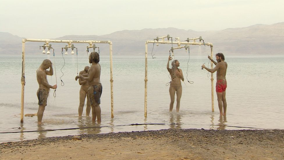 Visitors rinse the Dead Sea water and mud off themselves in public showers