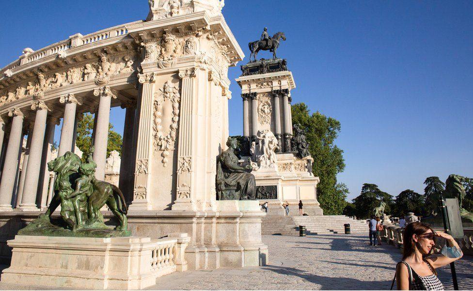 A woman covers her face from the sun and behind the Monument to Alfonso XII, which was built in 1922 in the Retiro park