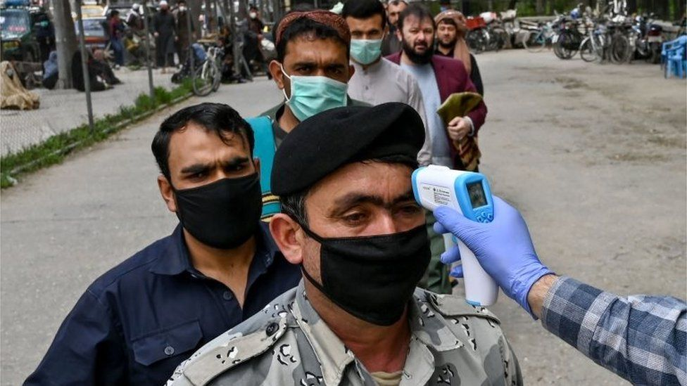 In this file photo taken on April 24, 2020 a health worker (R) checks the body temperature of a devotee as a preventive measure against the COVID-19 coronavirus before the Friday prayers on the first day of the Muslim holy month of Ramadan at Wazir Akbar Khan mosque in Kabul.