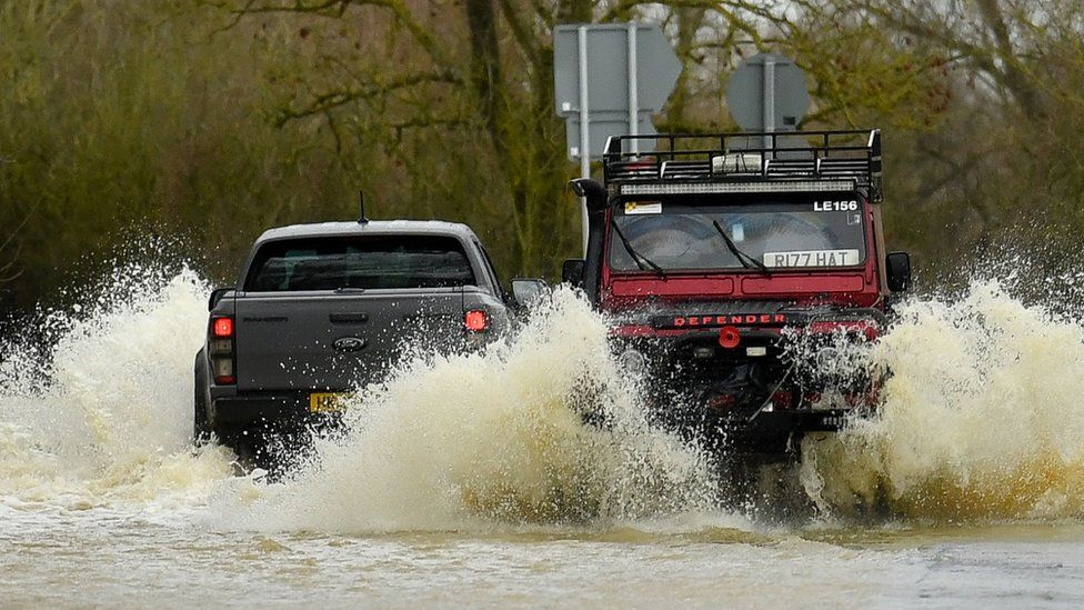 Cars driving through a flooded road