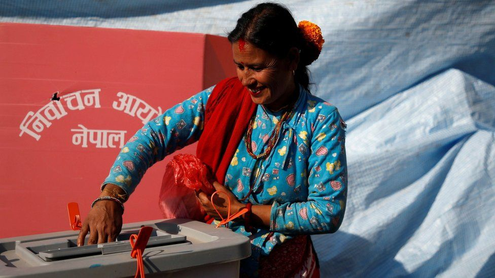 A woman smiles as she cast her vote during parliamentary and provincial elections in Sindhupalchok district, Nepal on 26 November 2017