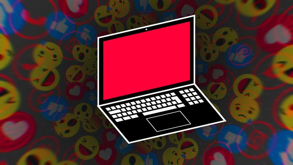 A laptop with a red screen against a background of emojis