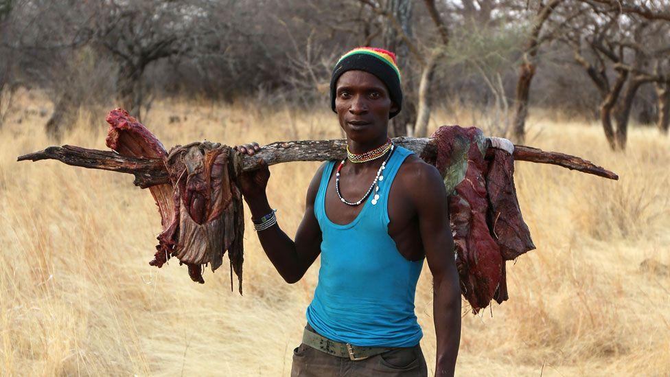 Homem hadza com pedaços de carne