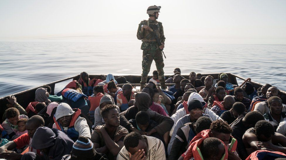 A Libyan coast guardsman stands on a boat during the rescue of migrants - archive shot 2017