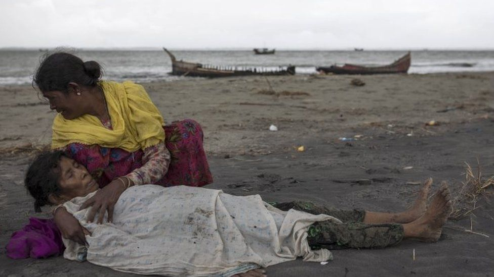 An elderly Rohingya woman is comforted after the wooden boat they were travelling on from Myanmar crashed into the Bangladeshi shore and tipped everyone out (12 September 2017)