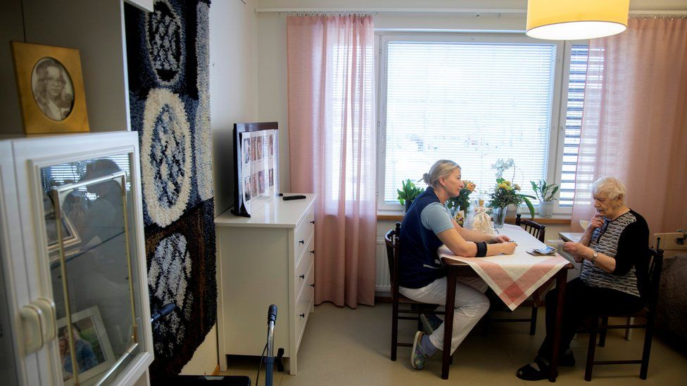 A nurse assists an elderly resident at the public care unit Heikanrinne in Forssa, Finland, 2 April 2019