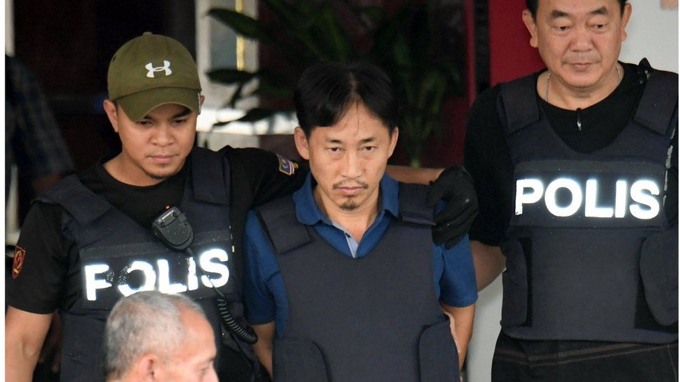 Ri Jong Chol in a bullet proof vest, alongside police officers also wearing bullet-proof vests, outside Sepang district police station in Sepang, Malaysia Friday, 3 March 2017.
