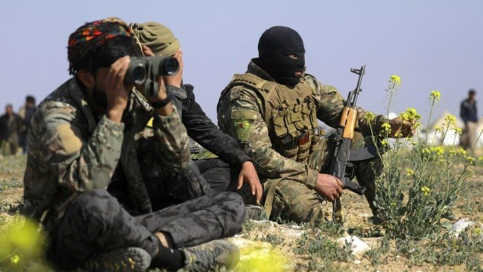 A member of the Kurdish-led Syrian Democratic Forces (SDF) looks through binoculars as he escorts a convoy carrying men, identified as Islamic State group fighters who surrendered, being transported out of IS's last holdout of Baghouz in Syria's northern Deir Ezzor province, on 20 February 2019.