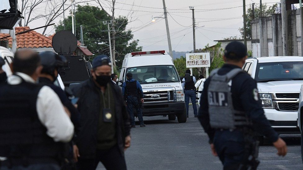 An ambulance is surrounded by police officers at a crime scene where gunmen killed at least 13 Mexican police officers in an ambush, in Coatepec Harinas, Mexico March 18, 2021