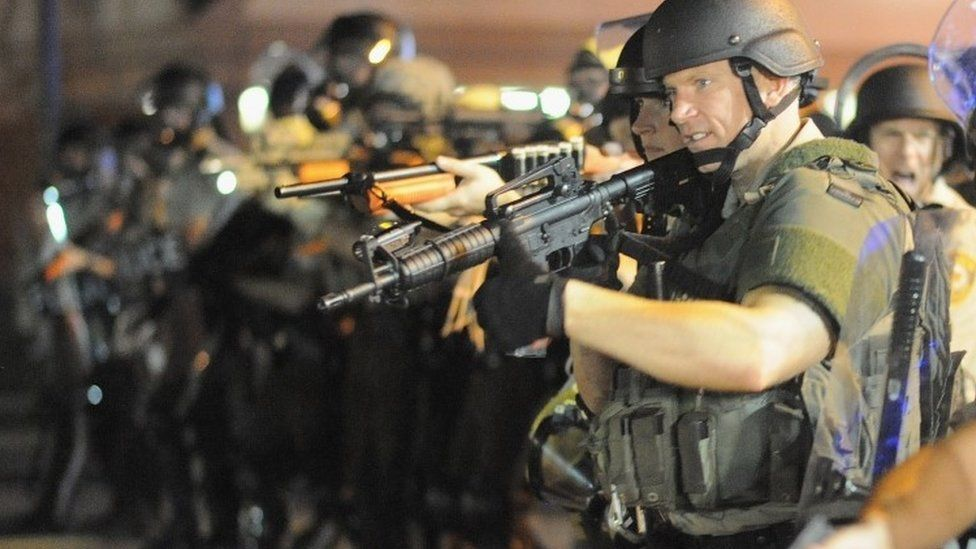Armed law enforcement officers watch on during a protest on West Florissant Avenue in Ferguson, Missouri (16 August 2014)