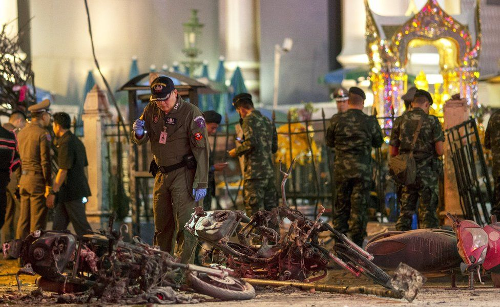 Experts investigate the devastated Erawan Shrine, 17 August 2015. A man in uniform looks at wrecked motorbikes, while others in uniform stand in the background.