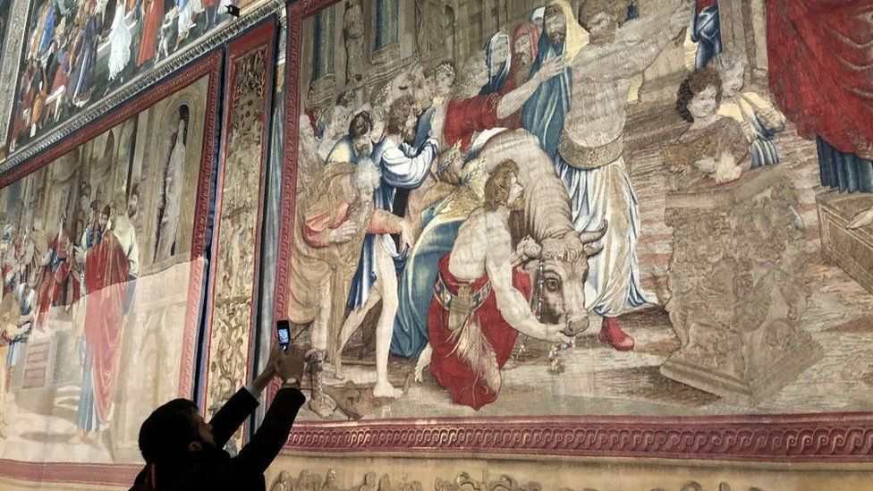 "Un hombre toma una imagen del tapiz ""El sacrificio de Listra"" de Rafael."