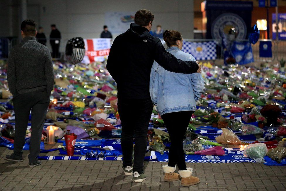 Mourners pause to pay tributes after the helicopter crash at The King Power Stadium on October 28, 2018 in Leicester, England