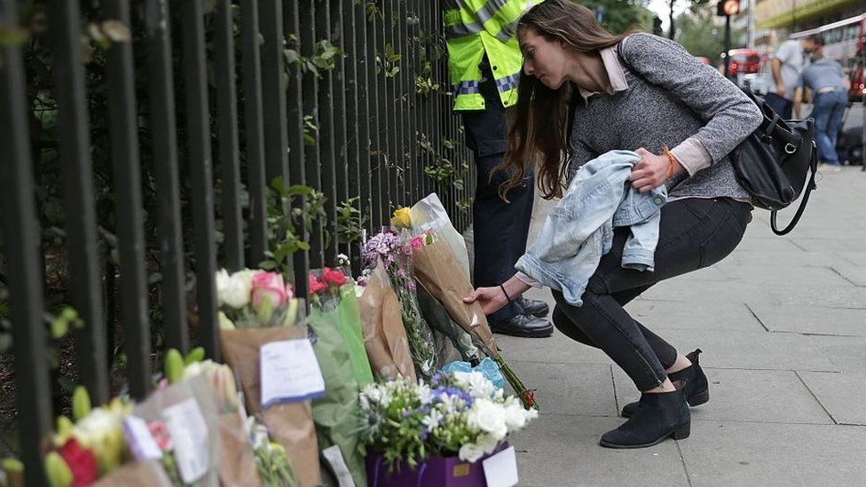 A woman lays flowers after a tourist was stabbed in Russell Square