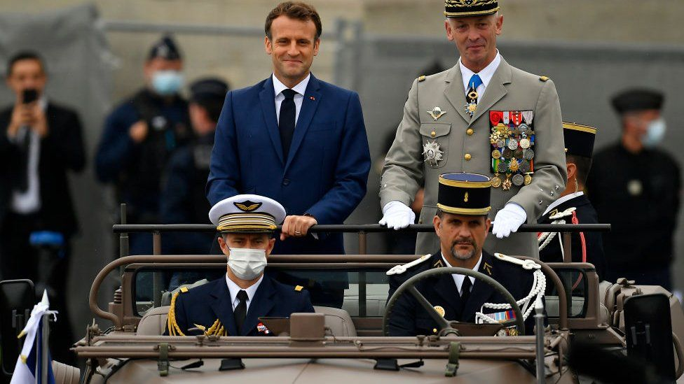 French President Emmanuel Macron and General Francois Lecointre Chief of Staff of the Armed Forces arrive on the command car during Bastille Day Military parade on July 14, 2021 in Paris, France