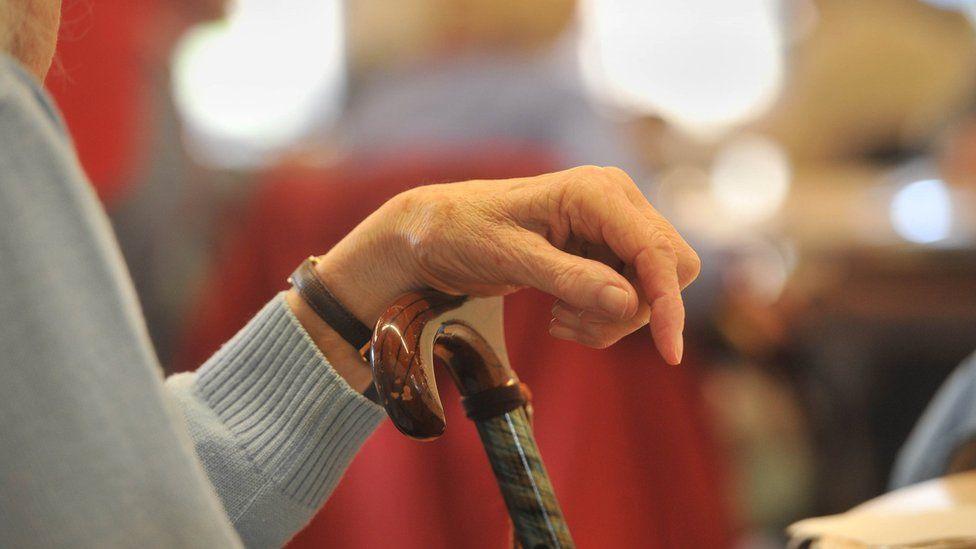 An elderly woman's hand on a walking stick