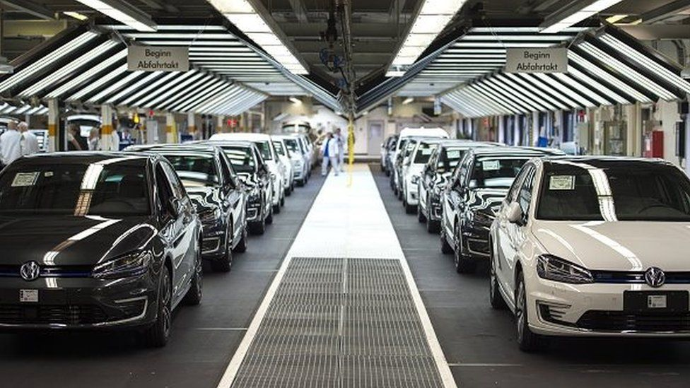 Employees of German car maker Volkswagen check cars at a assembly line of the VW plant in Wolfsburg