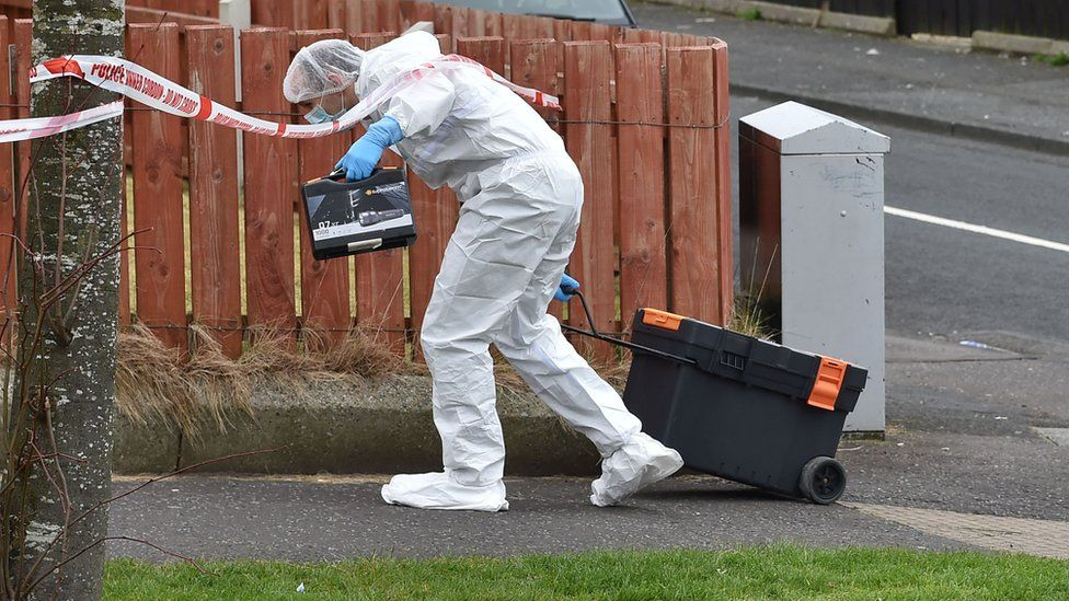 Forensic officers attended a flat in Derrycoole Way where one woman was killed